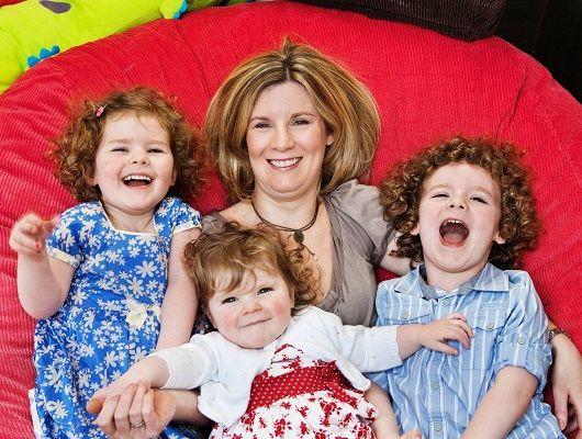 Мама з трьома дочками сидить на дивані