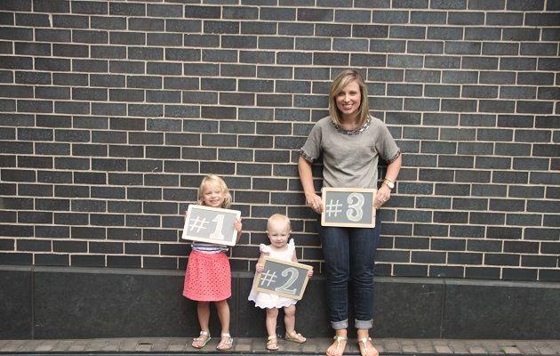 Вагітна жінка з двома дітьми стоять навпроти цегляної стіни