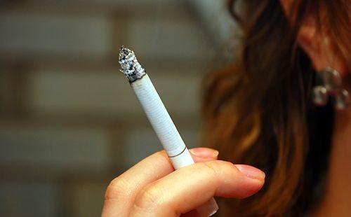 Дівочі пальці тримають сигарету