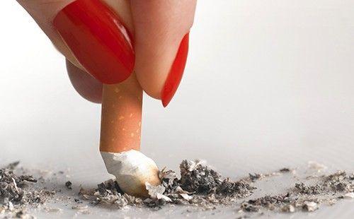 Жіночі пальці тиснуть сигарету в крихту