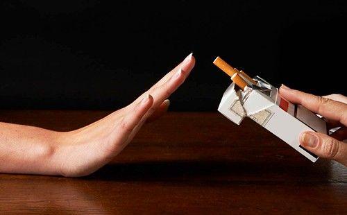 Дівчина робить негативний жест у відповідь на пропозицію закурити
