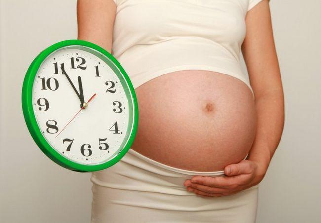 вагітна з годинником в руках