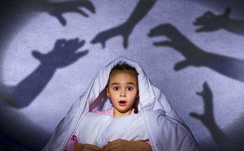 Дівчинка намагається сховатися під ковдрою від страшних тіней