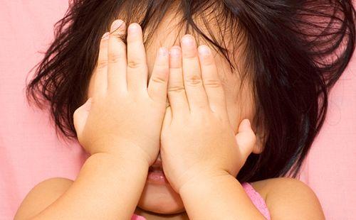 Дівчинка не хоче дивитися страшний мультик і закрила обличчя долонями